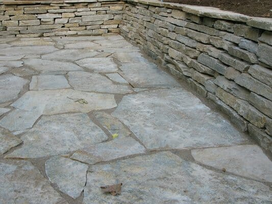 Custom designed flagstone patio with matching flagstone wall | EO Landscaping
